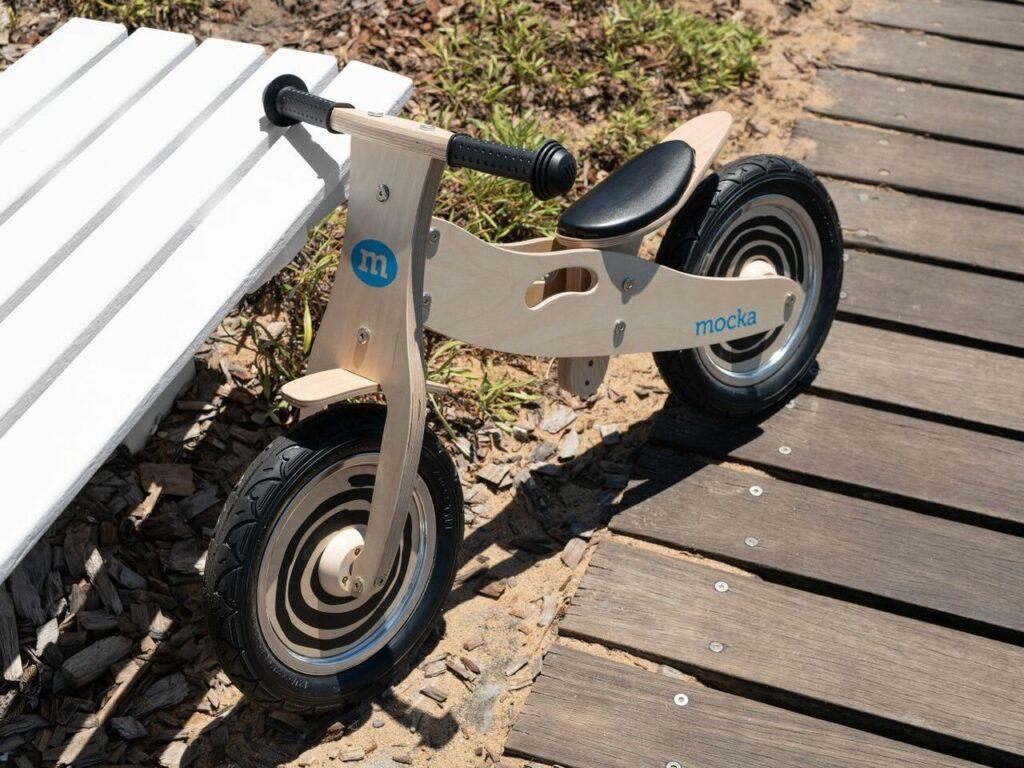 Wood Balance Bike leaning against a chair