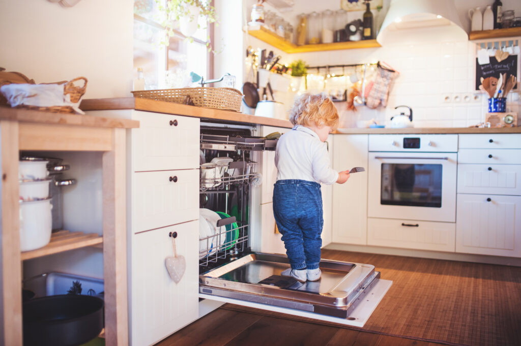 Toddler boy standing in a dishwasher
